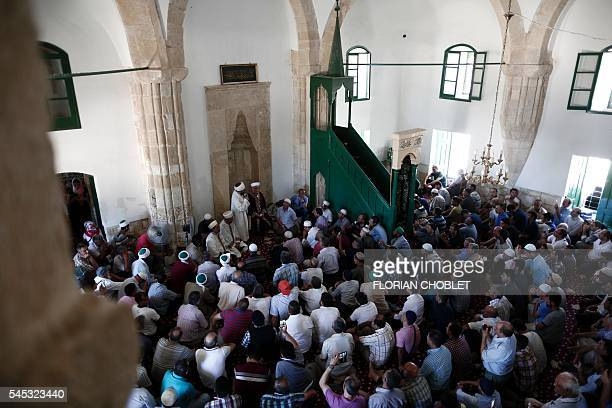 Turkish Cypriot Muslims sit the Hala Sultan Tekke mosque or the Mosque of Umm Haram in the Cypriot southeastern port city of Larnaca on July 7 during...