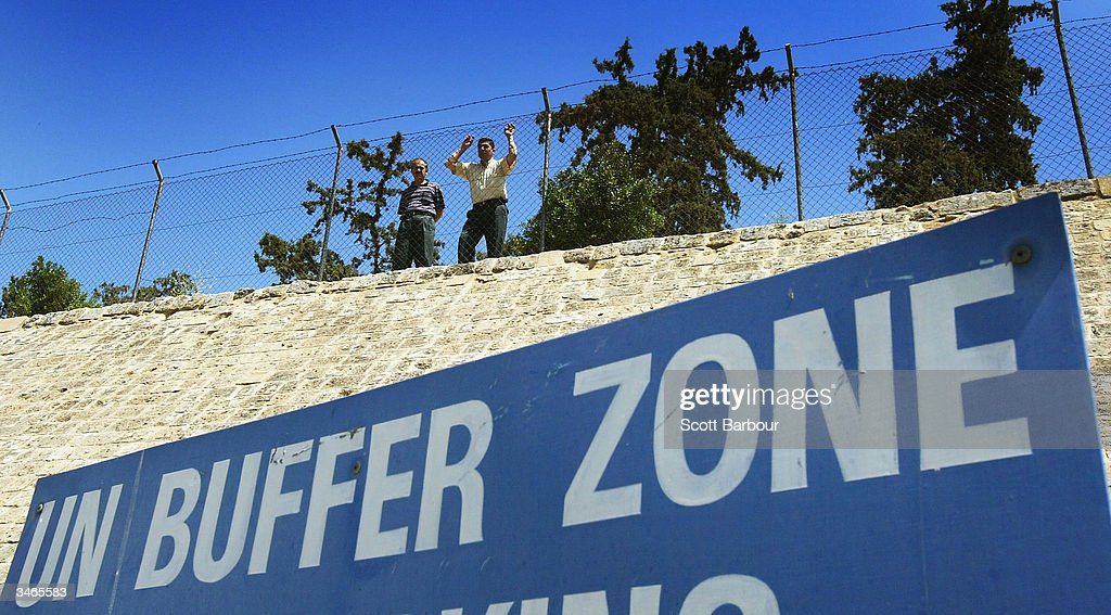 Turkish Cypriots look over the UN Buffer Zone into the Greek part of the divided city of Nicosia from the Turkish side on April 25 2004 in Nicosia...