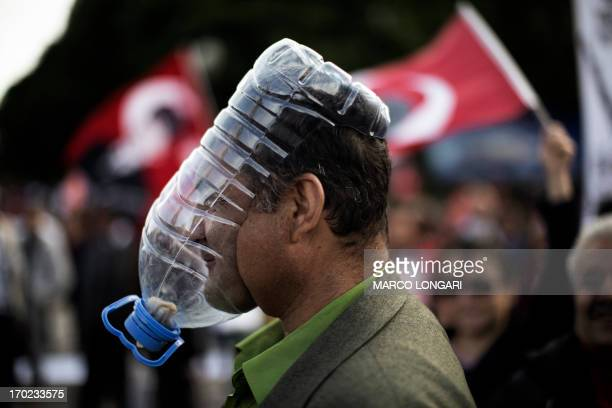 A Turkish demonstrator covers his face with a makeshift gas mask made from a large plastic bottle as protests resumed in Kizilay square in Ankara...