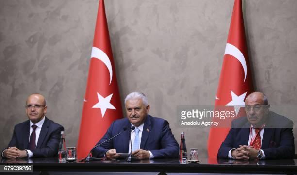 Turkish Deputy Prime Ministers Mehmet Simsek and Tugrul Turkes sit next to Turkish Prime Minister Binali Yildirim as he speaks during a press...