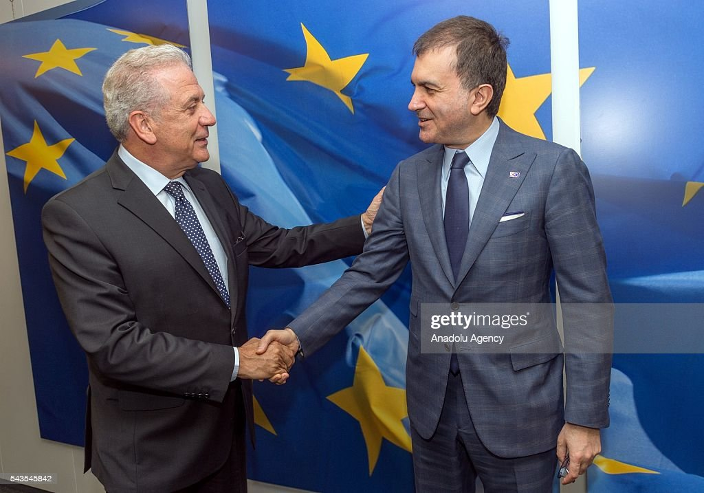 Turkish EU Minister Omer Celik (R) and EU Commissioner for Migration, Home Affairs and Citizenship Dimitris Avramopulos shake hands in Brussels, Belgium on June 29, 2016.