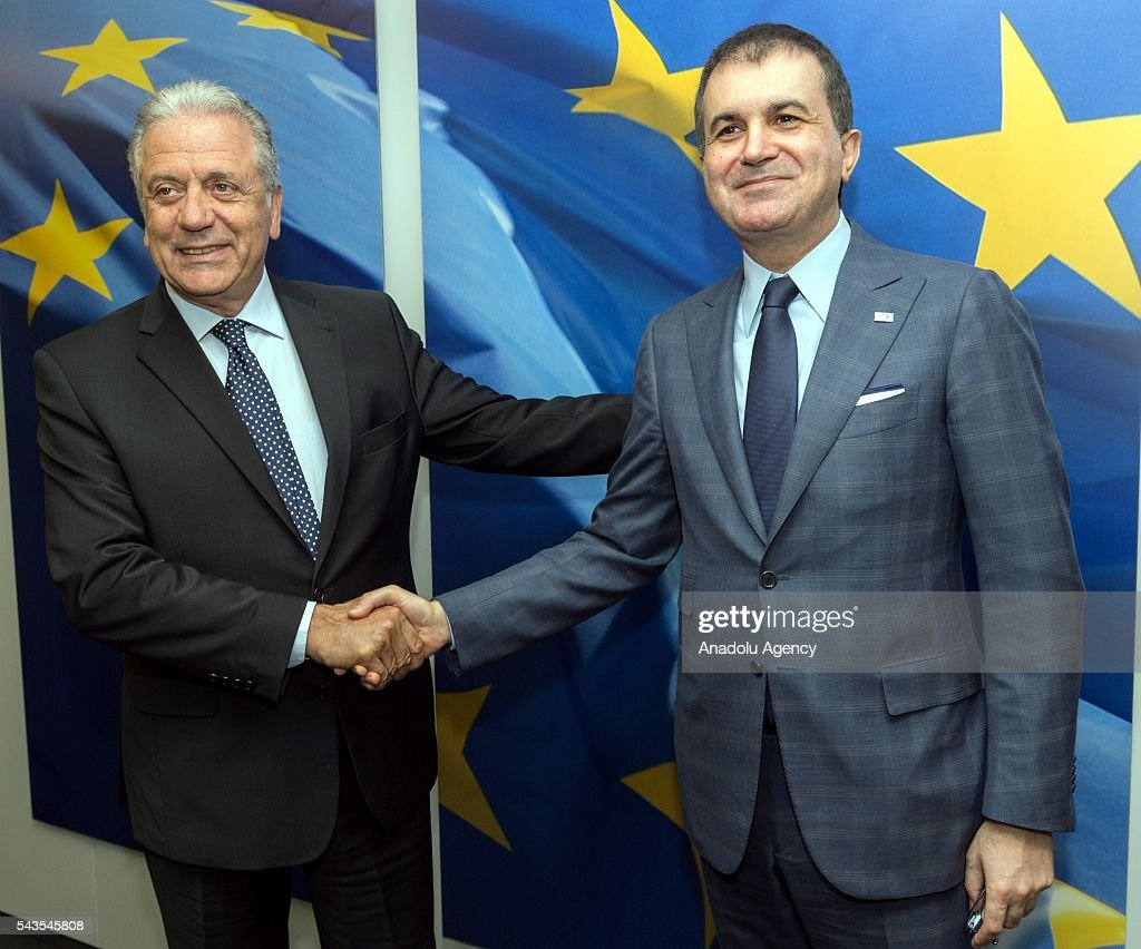 Turkish EU Minister Omer Celik (R) shakes hands with EU Commissioner for Migration, Home Affairs and Citizenship Dimitris Avramopulos in Brussels, Belgium on June 29, 2016.
