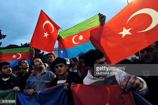 Turkish fans hold Azerbaijan and Turkish flags in front of the Ataturk Stadium in Bursa northern Turkey on October 14 few hours before Turkey faces...
