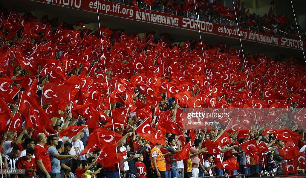 Turkish fans hold flags during the friendly football match between Turkey and Montenegro at Antalya Ataturk Stadium in Antalya, Turkey on May 29, 2016.