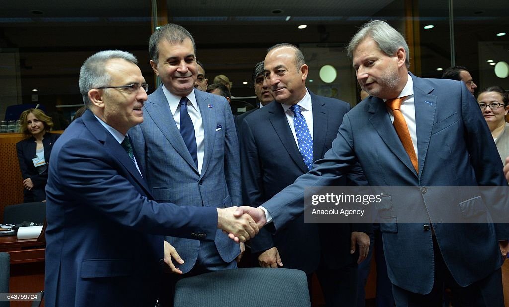 Turkish Finance Minister Naci Agbal (L) and Commissioner for European Neighbourhood Policy & Enlargement Negotiations, Johannes Hahn (R) shake hands at the Chapter 33 on financial and budgetary provisions as part of the EU-Turkey Intergovernmental Accession Conference in Brussels, Belgium on June 30, 2016.