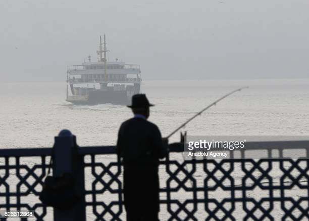 Turkish fishermen try to catch fishes during the heavy mist in Istanbul Turkey on July 27 2017