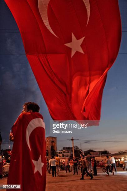 Turkish flag draped supporter of Turkish President Tayyip Erdogan stands at Istanbul's central Taksim Square on July 18 2016 in Istanbul Turkey Clean...
