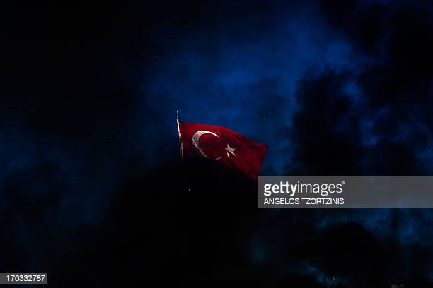 A Turkish flag flies as smoke billows from burning vehicles on Taksim square in Istanbul on June 11 2013 Riot police reentered Istanbul's protest...