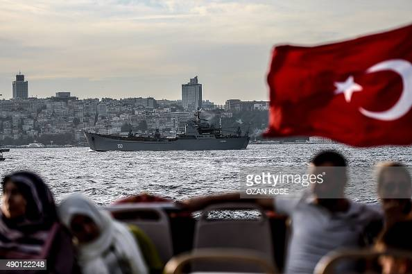 A Turkish flag flies on a ferry as Russian warship the BSF Saratov 150 sails through the Bosphorus off Istanbul en route to the eastern Mediterranean...