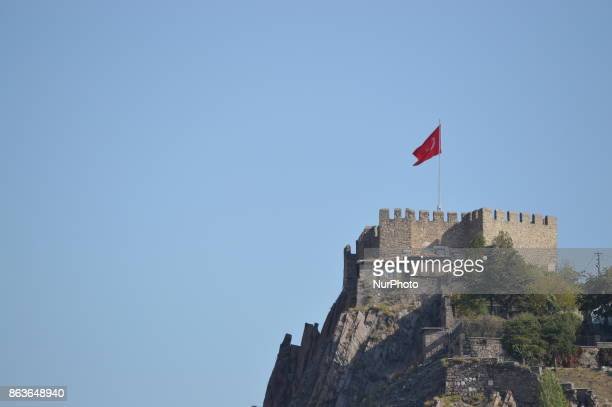 A Turkish flag waves over the Ankara Castle in the historic Ulus district of Ankara Turkey on October 20 2017