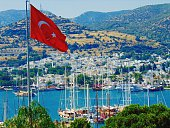 Turkish Flag With Boats Moored In Sea By City