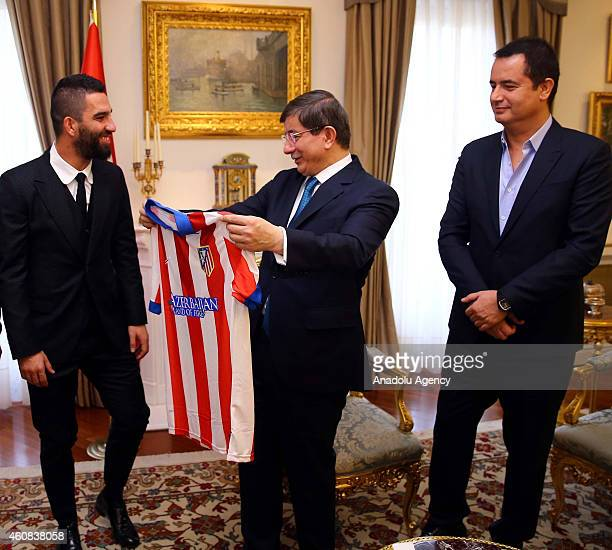 Turkish footballer Arda Turan playing for Spanish outfit Atletico de Madrid presents the uniform of his team to Turkish Prime Minister Ahmet...