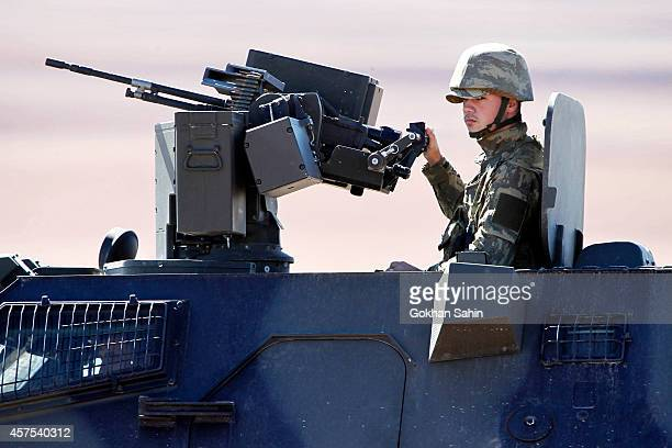 A Turkish forces soldier rides atop an armored vehicle as he patrols the TurkishSyrian border October 20 2014 in the southeastern town of Suruc in...
