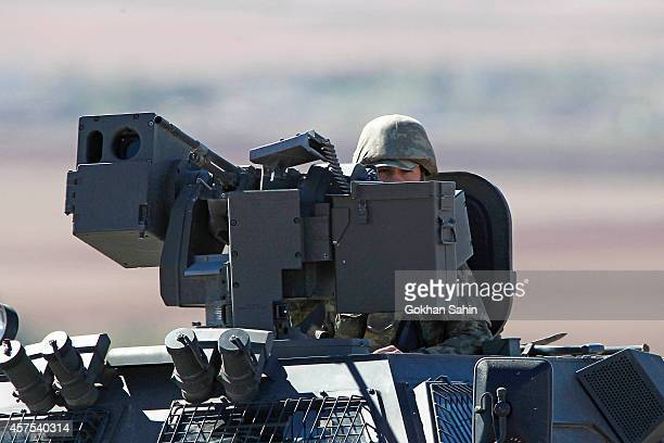 Turkish forces soldier rides atop an armored vehicle as he patrols the TurkishSyrian border October 20 2014 in the southeastern town of Suruc in...