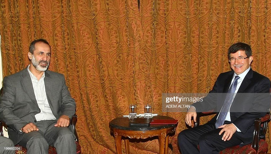 Turkish Foreign Minister Ahmet Davutoglu,(R), and head of Syrian National Coalition for Opposition Mouaz al-Khatib pose before a meeting in Ankara, on November 23, 2012.