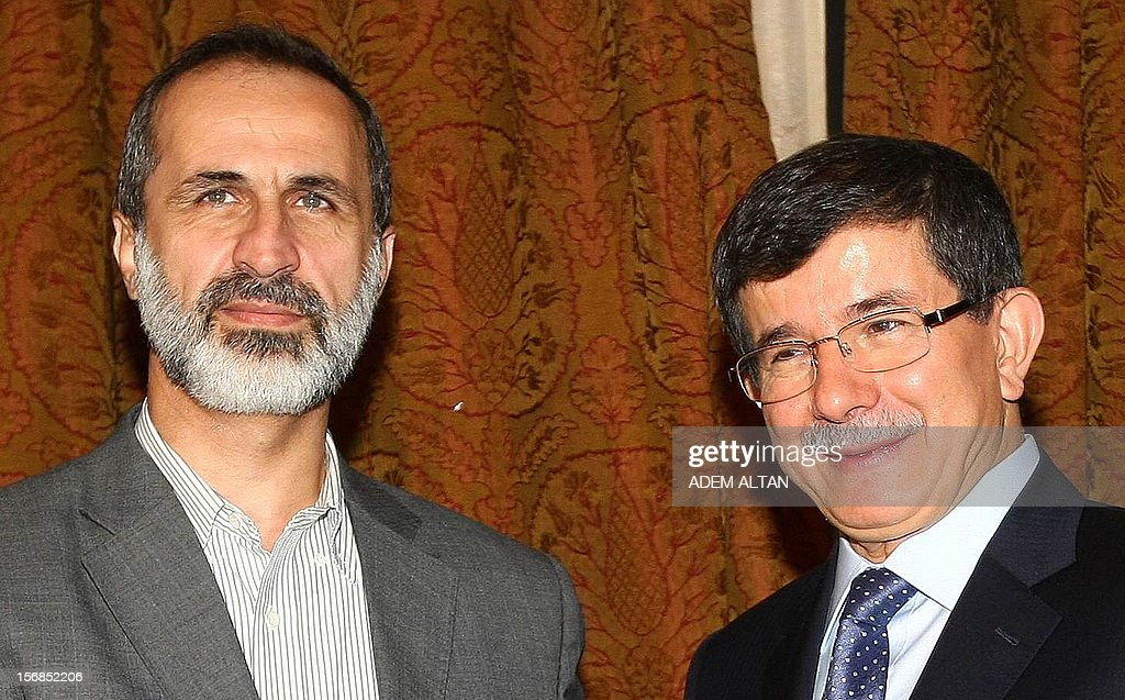 Turkish Foreign Minister Ahmet Davutoglu,(R), and head of Syrian National Coalition for Opposition Mouaz al-Khatib pose before a meeting in Ankara, on November 23, 2012. AFP PHOTO/ADEM ALTAN