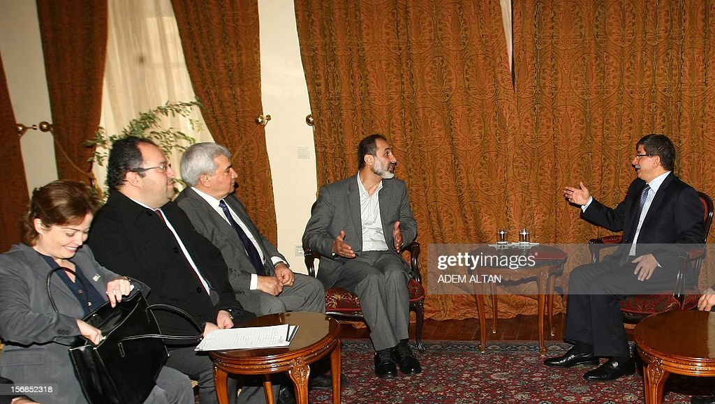 Turkish Foreign Minister Ahmet Davutoglu,(R), and head of Syrian National Coalition for Opposition Mouaz al-Khatib talk with other members before a meeting in Ankara, on November 23, 2012.