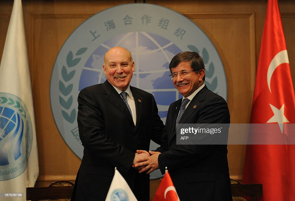 Turkish Foreign Minister Ahmet Davutoglu (R) and Shanghai Cooperation Organization (SCO) Secretary General Dmitry Mezentsev shake hands after signing an agreement on the sidelines of at the Istanbul Process Ministers' Conference in the Kazakh capital Astana, on April 26, 2013. Turkish Foreign Minister signed today documents granting Turkey a partner status in SCO. the media reported.