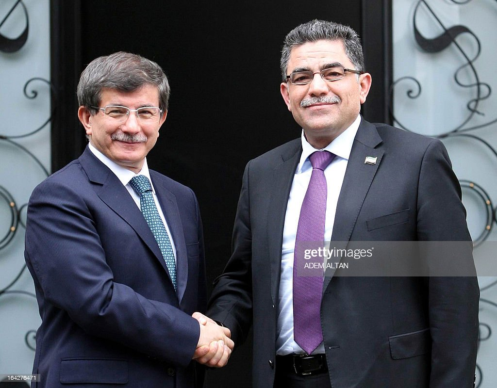 Turkish Foreign minister Ahmet Davutoglu (L) shakes hands with Syrian opposition prime minister Ghassan Hitto prior to a meeting in Ankara, on March 22, 2013. In a new challenge to the regime of Syrian President Bashar al-Assad, the Syria's main opposition National Coalition appointed Hitto after some 14 hours of closed-door consultations in the Turkish city of Istanbul on March 19, 2013.