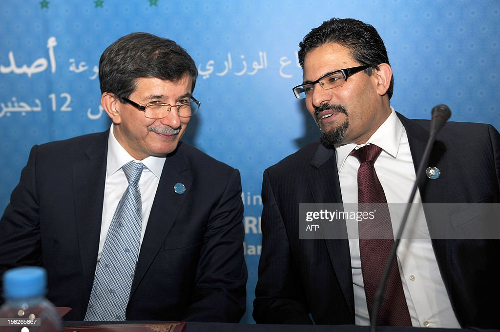 Turkish Foreign Minister Ahmet Davutoglu (L) talks with Tunisian Minister of Foreign Affair Rafik Abdessalem at the Friends of Syria conference in Marrakesh on December 12, 2012. The talks on the 21-month conflict rocking Syria brought together representatives from 114 countries, including about 60 ministers, the Syrian opposition and international organisations.