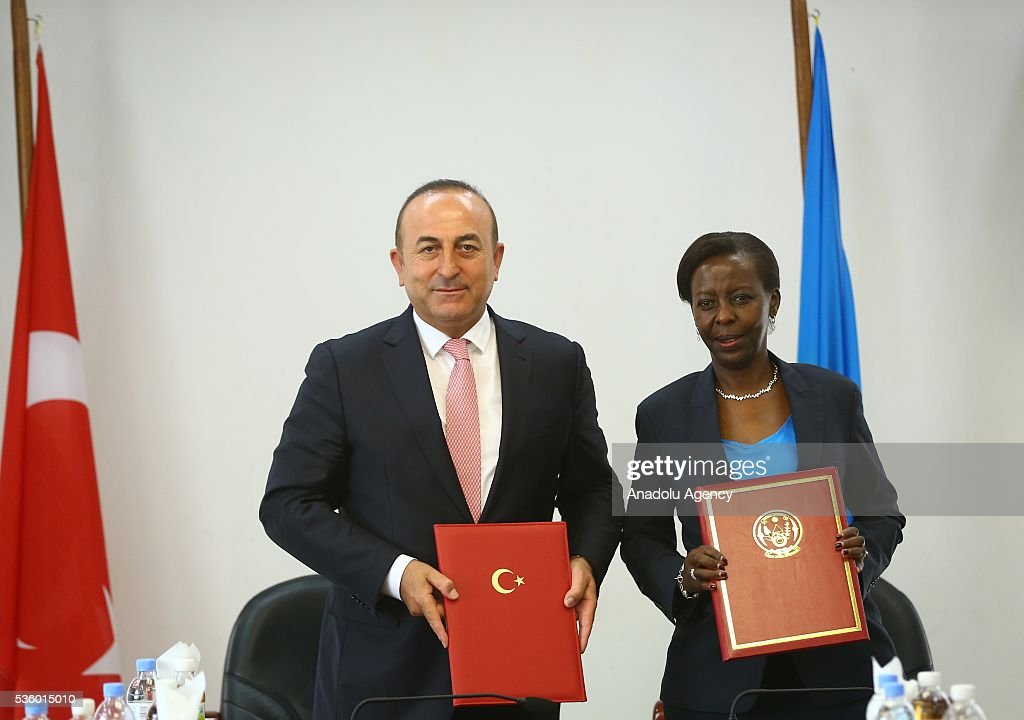 Turkish Foreign Minister Cavusoglu (L) and Minister of Foreign Affairs and Cooperation of Rwanda Louise Mushikiwabo (R) sign agreements on education cooperation, visa exemption to diplomatic passports and a memorandum of understanding after their meeting in Kigali, Rwanda on May 31, 2016.