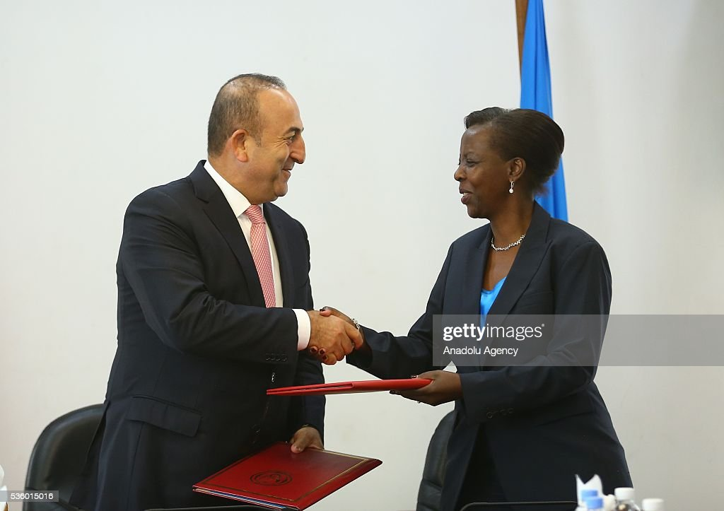 Turkish Foreign Minister Cavusoglu (L) and Minister of Foreign Affairs and Cooperation of Rwanda Louise Mushikiwabo (R) shake hands after signing agreements on education cooperation, visa exemption to diplomatic passports and a memorandum of understanding following their meeting in Kigali, Rwanda on May 31, 2016.