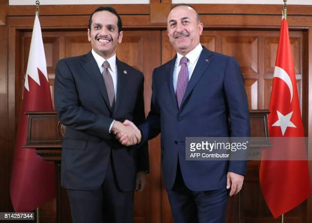 Turkish Foreign Minister Mevlut Cavusoglu and Foreign Minister of Qatar Mohammed bin Abdulrahman bin Jassim AlThani shake hands after a joint press...