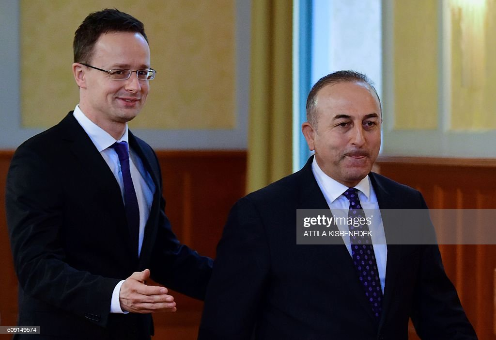Turkish Foreign Minister Mevlut Cavusoglu (R) and Hungary's Minister of External Economy and Foreign Affairs Peter Szijjarto (L) arrive at the Conference Hall of the ministry building in Budapest on February 9, 2016 prior to their joint international press conference. The Turkish foreign minister is on a one-day visit to Hungary. / AFP / ATTILA KISBENEDEK