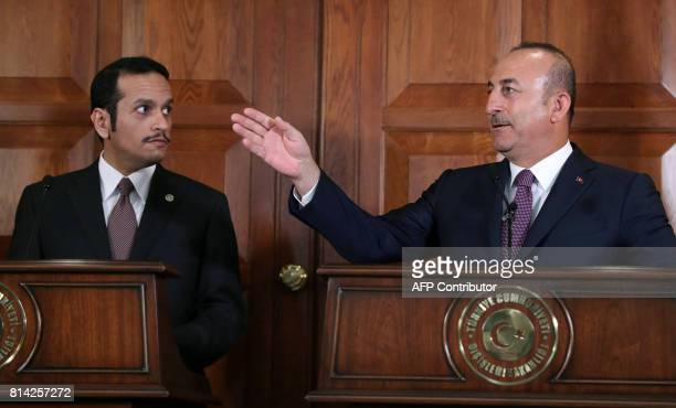 Turkish Foreign Minister Mevlut Cavusoglu is watched by Foreign Minister of Qatar Mohammed bin Abdulrahman bin Jassim AlThani as he gestures while...