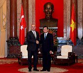 Turkish Foreign Minister Mevlut Cavusoglu meets Vietnamese President Truong Tan Sang at the presidential palace in Hanoi Vietnam on March 17 2015