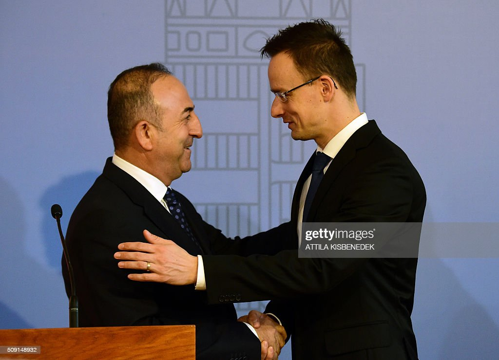 Turkish Foreign Minister Mevlut Cavusoglu (L) shakes hands with Hungary's Minister of External Economy and Foreign Affairs Peter Szijjarto (R) in Budapest on February 9, 2016 after their joint international press conference. The Turkish foreign minister is on a one-day visit to Hungary. / AFP / ATTILA KISBENEDEK