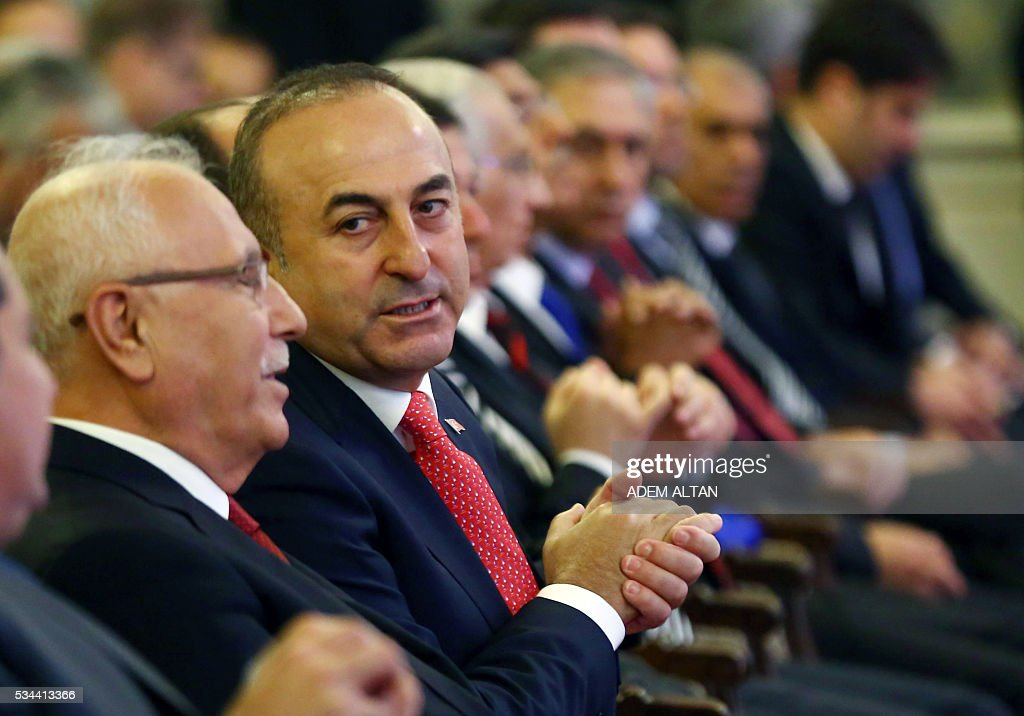 Turkish Foreign Minister Mevlut Cavusoglu (2nd L) sits among Turkmens before addressing the Syrian Turkmen Assembly meeting in Ankara, on May 26, 2016. Syrian Turkmens gathered to discuss the latest developments in Syria. / AFP / ADEM