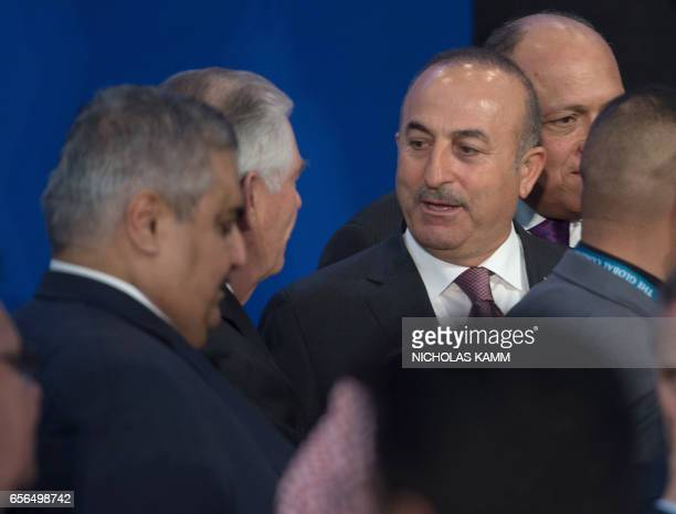 Turkish Foreign Minister Mevlut Cavusoglu speaks with US Secretary of State Rex Tillerson after posing for a photo at a meeting of the coalition to...