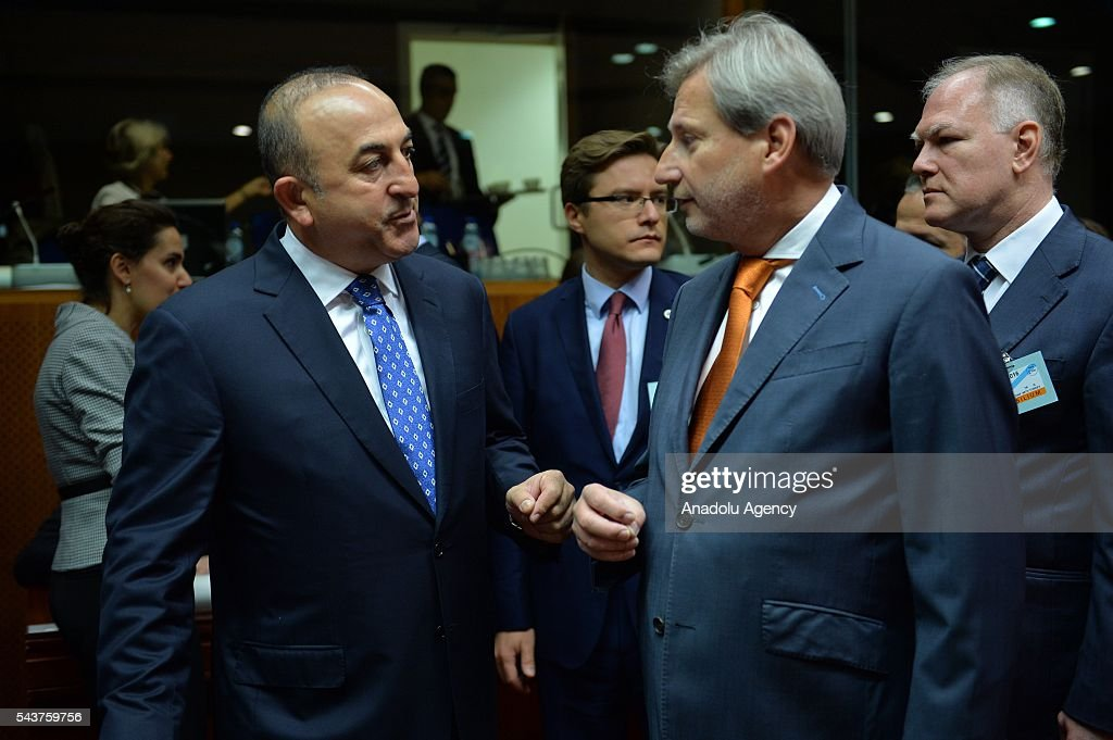 Turkish Foreign Minister Mevlut Cavusoglu (L) talks with Commissioner for European Neighbourhood Policy & Enlargement Negotiations, Johannes Hahn (R2) at the Chapter 33 on financial and budgetary provisions as part of the EU-Turkey Intergovernmental Accession Conference in Brussels, Belgium on June 30, 2016.