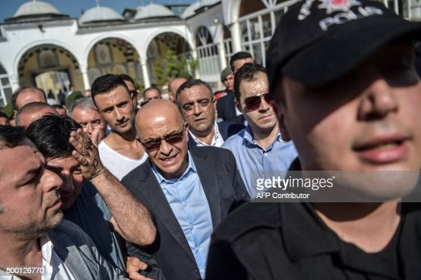 Turkish former journalist turned CHP lawmaker Enis Berberoglu escorted by a Turkish Riot police officers attends his stepfather's funeral on June 23...