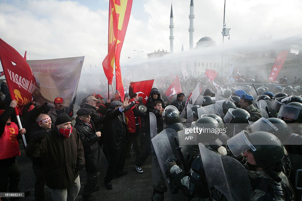 Turkish gendarmerie fire water cannon and tear gas as they clash with hundreds of protesters trying to enter a courthouse in Silivri near Istanbul on February 18, 2013 where prosecutors are scheduled to deliver their final arguments in the case against 275 people accused of plotting to overturn the Islamic-leaning government. A verdict in the four-year long case involving 275 defendants, including Turkey's former military chief Ilker Basbug and other army officers as well as lawyers, academics and journalists, is expected in the coming weeks. The defendants face dozens of charges, ranging from membership in an underground 'terrorist organisation' known as Ergenekon and instigating an armed uprising against Erdogan and his Justice and Development Party (AKP), which came to power in 2002. AFP PHOTO/STR