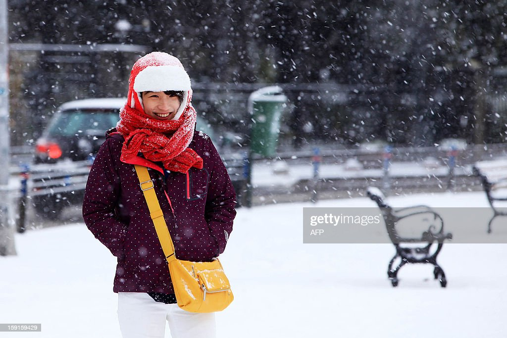 A Turkish girl smiles while walking during snowfalls in Istanbul on January 9, 2013. Heavy snowfall blanketed Turkey's commercial hub Istanbul, a city of 15 millions, paralysing daily life, disrupting air traffic and land transport. AFP PHOTO/MIRA