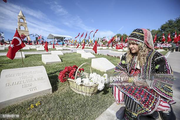 Turkish girl wearing traditional costume prays and places flowers to Martyrs' cemeteries during a ceremony marking the 101st anniversary of the...