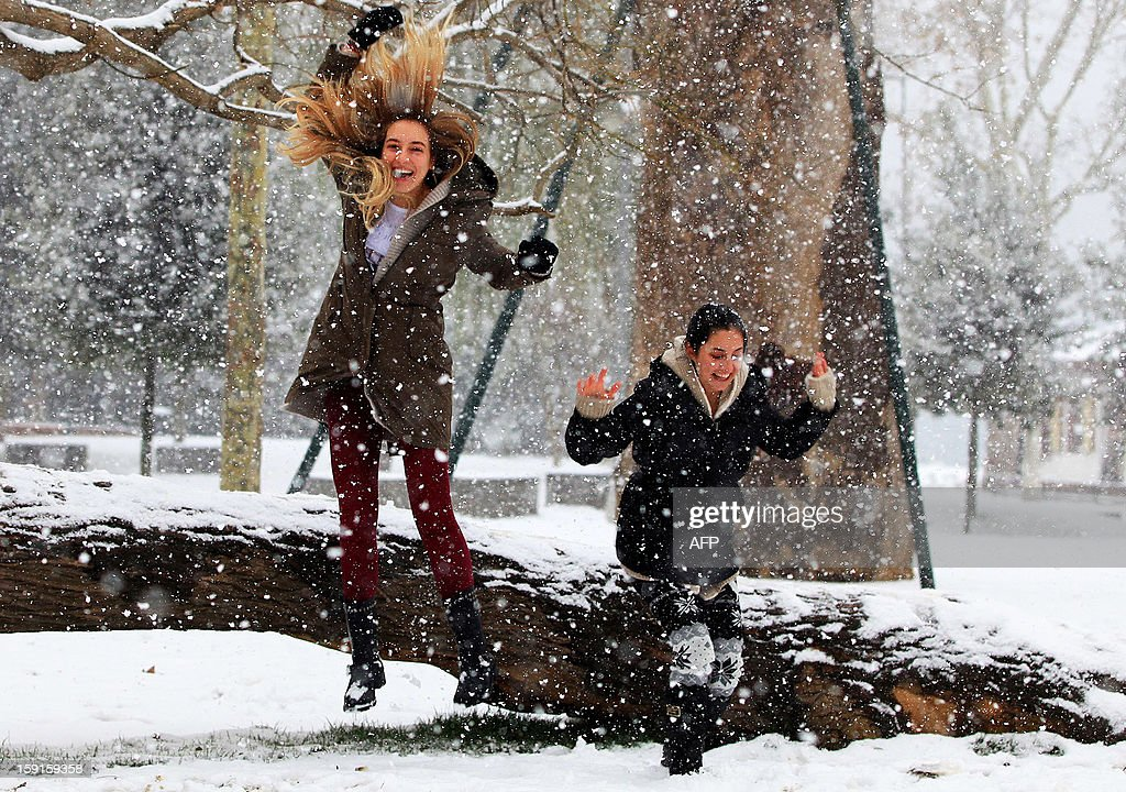 Turkish girls celebrate as snow falls over Istanbul, on January 9, 2013. Heavy snowfall blanketed Turkey's commercial hub Istanbul, a city of 15 million, paralysing daily life and disrupting air traffic and land transport. AFP PHOTO / MIRA