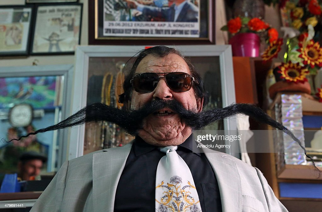 Turkish hairdresser Haci Kilic of Turkey poses with his 1.5 meter long mustache in his barbershop in Erzurum, Turkey on March 15, 2014. Ahmet Kilic uses various medicines for his mustache and has not cut it for thirty years. During the working, Kilic wraps his mustache to his head.