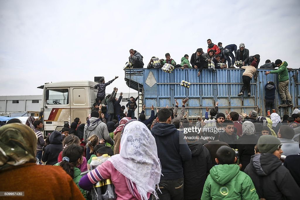 Turkish humanitarian aid organization members distribute humanitarian aids for Syrians, who fled bombing in Aleppo at a tent city close to the Bab al-Salam border crossing on Turkish-Syrian border near Azaz town of Aleppo, Syria on February 13, 2016. Russian airstrikes have recently forced some 40,000 people to flee their homes in Syrias northern city of Aleppo.