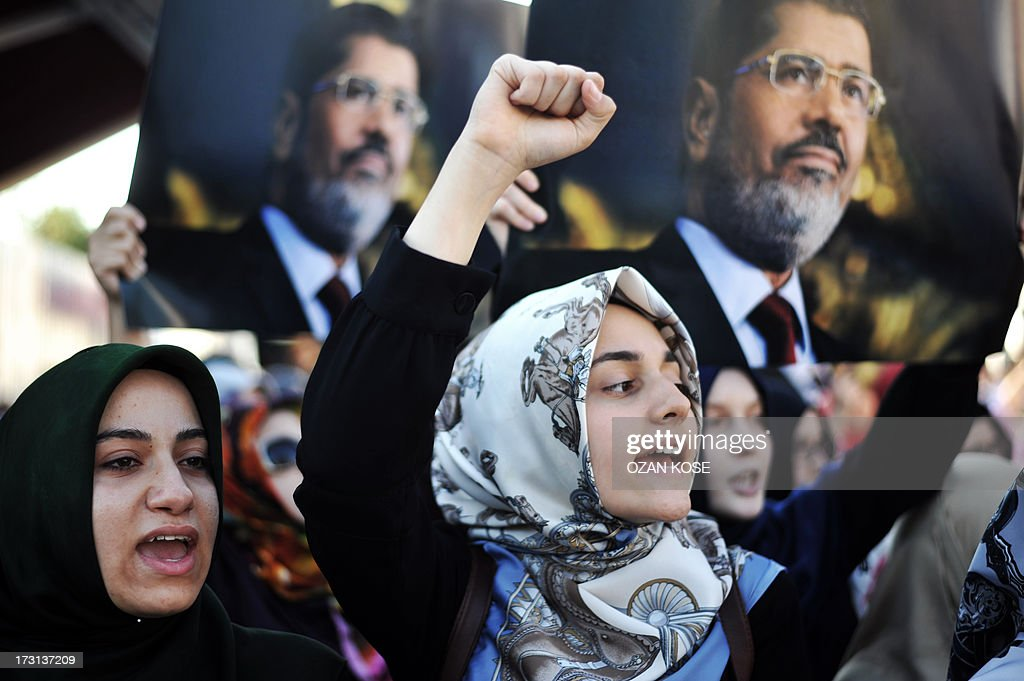 Turkish Islamist women protesters chants slogans as they hold posters of ousted Egyptian President Mohamed Morsi during a pro-Morsi demonstration in front of the Fatih Mosque in Istanbul, on July 8, 2013. Fifty-one loyalists of Egypt's ousted president were killed on July 8 while demonstrating against last week's military coup, triggering an Islamist uprising call and dashing the army's hopes for an interim civilian administration. The Muslim Brotherhood, which has led demonstrations against Wednesday's overthrow of Islamist president Mohamed Morsi, said its supporters were 'massacred' by troops and police during dawn prayers in Cairo..
