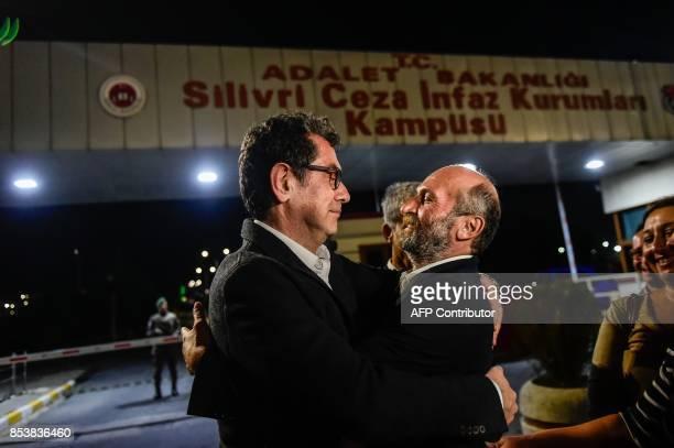 Turkish journalist Kadri Gursel embraces newspaper Cumhuriyet's Ankara bureau chief Erdem Gul after his release from Silivri prison on September 26...