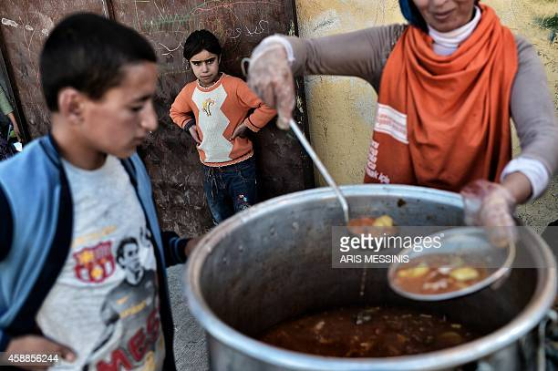 A Turkish Kurd volunteer serves food at a refugee camp in the Turkish town of Suruc in the Sanliurfa province on November 12 2014 Kurdish forces...