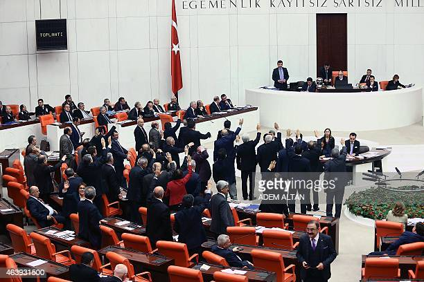 Turkish lawmakers raise their hands during a debate on a legislation to boost police powers against protesters at the Turkish parliament in Ankara on...