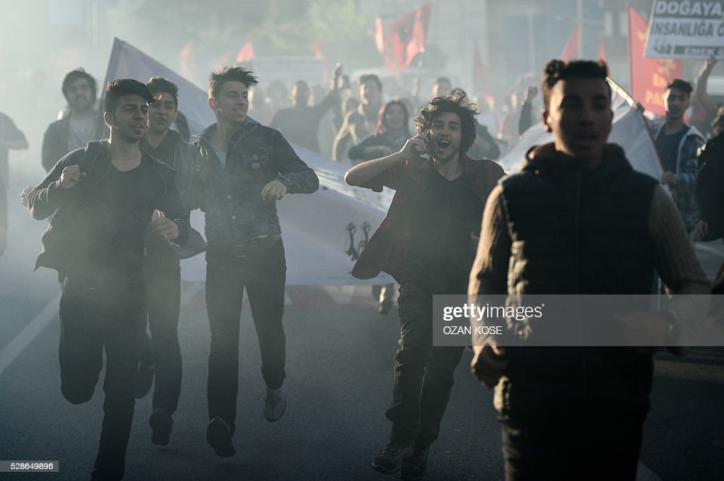 Turkish leftist demostrators run with torches and EMEP flags on May 6, 2016 at Dolmabahce in Istanbul during a demonstration on the anniversary of the execution of Deniz Gezmis (1947-1972), one of the founders of the People's Liberation army of Turkey (THKO). Gezmis was sentenced to death and hung in a Ankara jail on May 6, 1972. / AFP / OZAN
