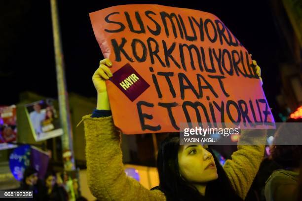 A Turkish leftist woman holds a placard that reads 'We don't shut up we aren't afraid we don't obey'' as they march in support of ''No'' campaign at...