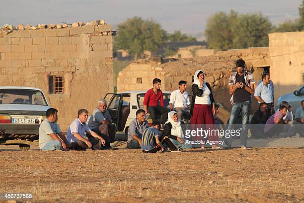 Turkish local residents watch the smoke rising from Syria's Ayn alArab city after the shelling at the clashes between the Islamic State of Iraq and...
