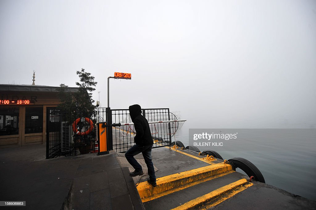 A Turkish man walks at Kabatas landing early on January 4, 2013, in Istanbul, after heavy fog restricted boat traffic on the Bosphorus.