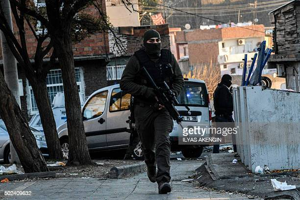 Turkish masked plain clothes police officer patrols a street during a clash between Kurdish activists and Turkish police in the historical Sur...